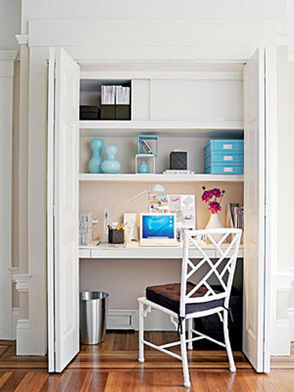 Desk area with what wall and shelves, hardwood floor, laptop, office items on tiers.