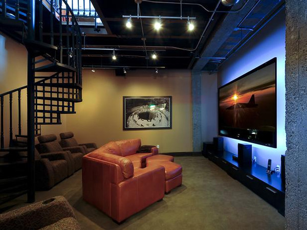 A condo space is optimized into a multi purpose media room while retaining its urban industrial feel.