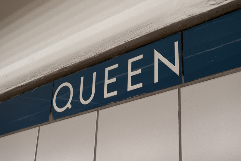 """One of the few surviving examples of the Toronto Subway's original vitrolite tiles can be found in the blue strip near the ceiling of Queen station's platform.  The tiles have an interesting, """"glassy"""" reflective quality and are no longer manufactured.  Notice also the unique 50s modernist font designed for the line's 1954 opening."""