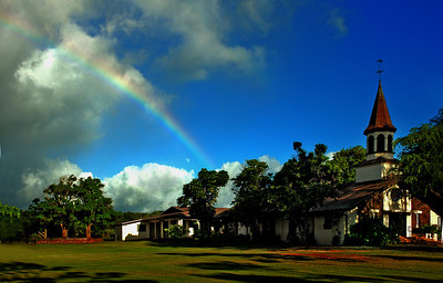 A rainbow over the large grassy area touches the church North Shore of O'ahu, Hawai'i