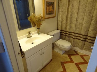 Another view of the bathroom reveals the contrasting patterned marble floor tiles.