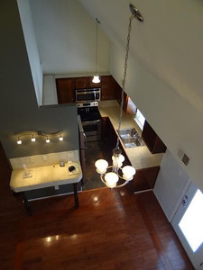 A view from the loft looking down on the breakfast area and kitchen. All the premium quality lighting fixtures in this view are on dimmers for dramatic lighting effects ranging from full-bright for cooking to dimmed for a romantic dinner for two. The double paned door opens to a small balcony overlooking 4th street.