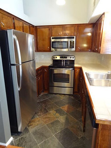The new, just-installed stainless steel refrigerator, electric range with ceramic glass cooktop, and microwave oven / range hood. The counter tops and backsplash are tile, the floor is slate.