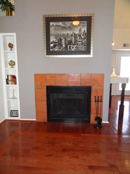 The living room view of the fireplace reveals the patterned hardwood floor.