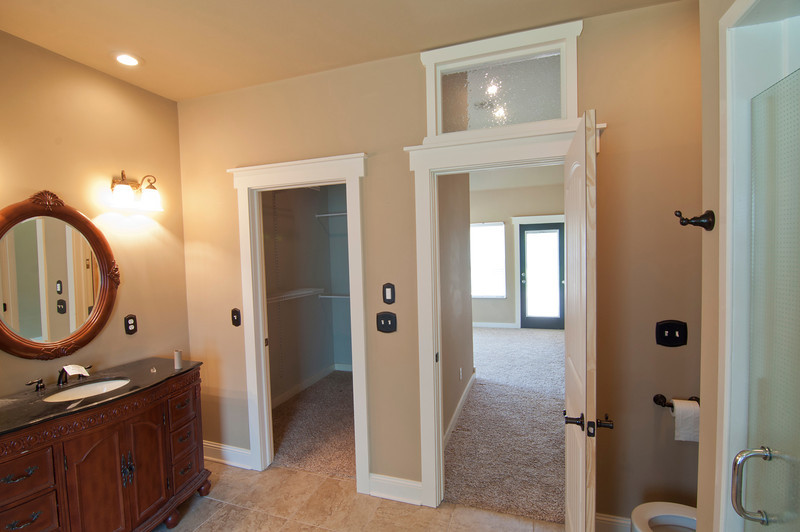 view into the closet and bedroom. Shower connects to the man's bathroom with another shower door on the other side.