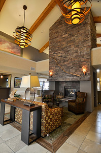 Fireplace in remodeled hotel lobby with new chandeliers, new furniture, light fixtures, artwork and custom original cloud photography by Pat Kofahl of Esprit Decor Gallery & Framing.