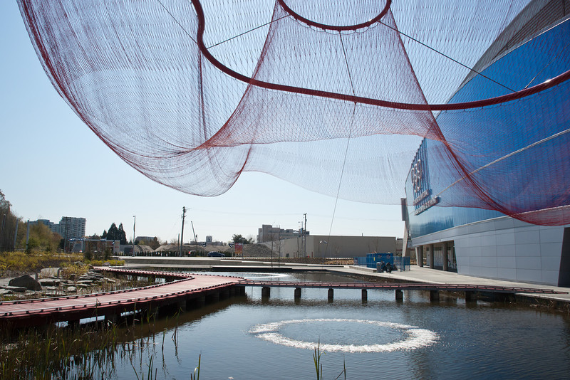 The pond on the east side of the Richmond Olympic Oval features ring-type fountains, fully accessible boardwalks, and interesting ornamental netting.