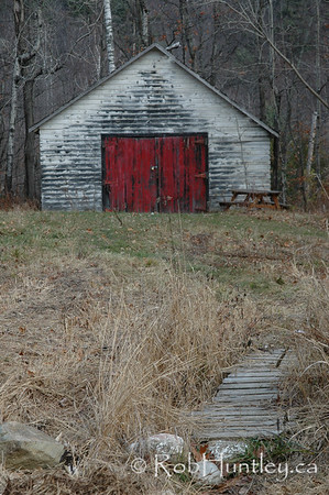 Rustic old shed with red and white peeling paint.