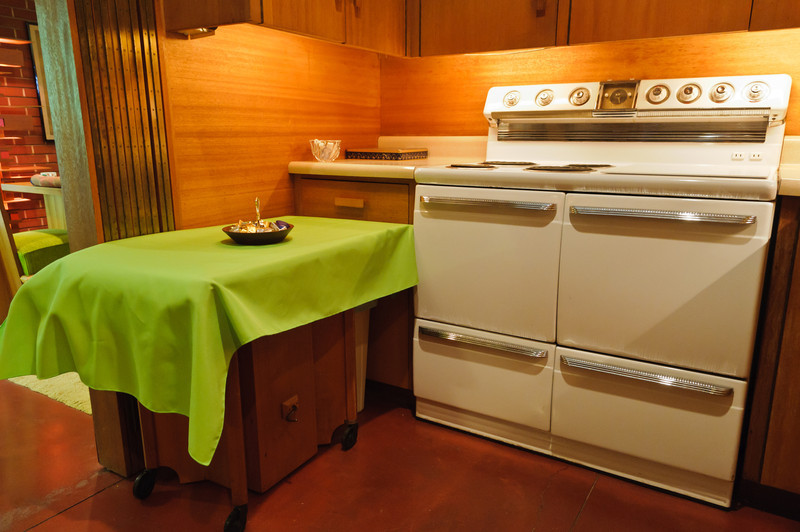 The kitchen hosts an original stove as well as the leaf of the dining room table which is also used as a utility table.