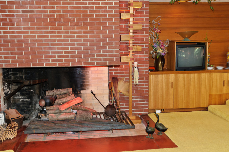 The fireplace's design makes it seem as if its floating in space.  The carpenters did not believe the design was possible, but Wright proved them wrong.  To the right is the hidden television.  When the Christian's received their house plans, they did not own a TV.  However, Wright's ability to see how the TV would change culture said the Christians would eventually own three.  The problem was the TV does not fit the architecture of the house, so it is placed in the nearby cabinet so it can be hidden when not in use.
