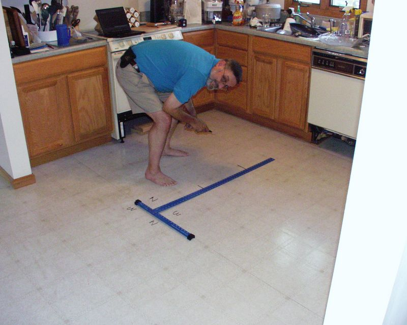 Rick lays out the patten on the floor in marker. Note the laptop: he had produced a full floor diagram to calculate how many tiles to buy. On the floor the North/West orientation marks are for the patterned tiles so that using times with the same pattern won't be obvious in the long run.