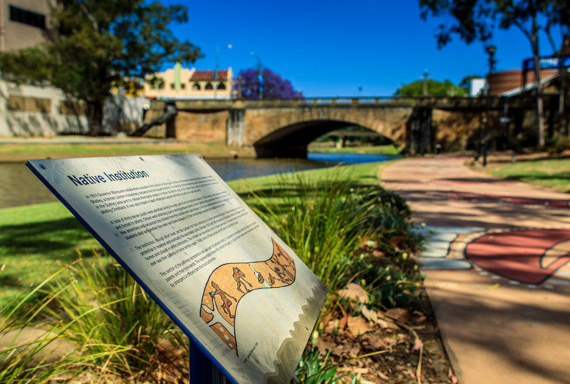 The mural tells the story of the school known as the 'Native Institution' (1814-1822), an early attempt to force Aboriginal children to conform to a British way of life. The bridge in the background is the Lennox Bridge, built 1836-1839.