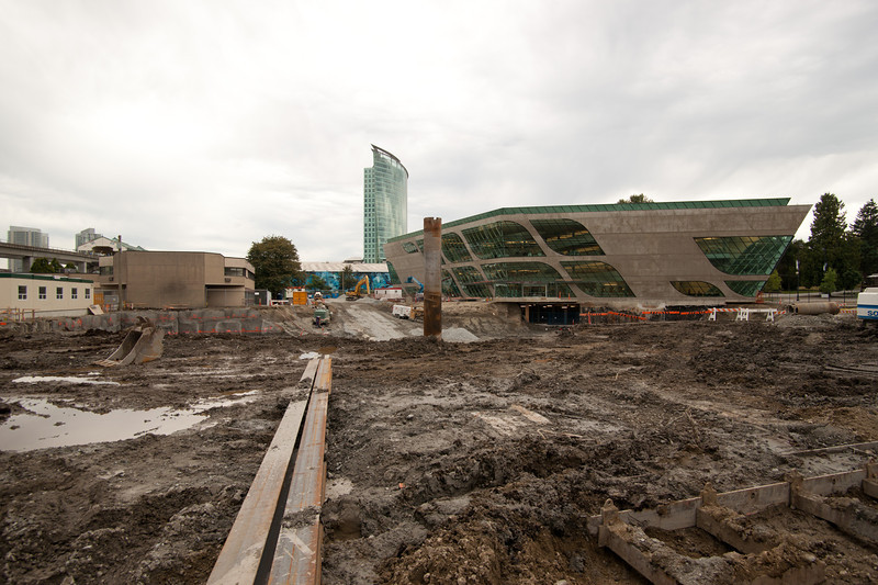 """The new Surrey Public Library as seen from the north.  The """"Central City"""" tower, also by Bing Thom, is seen in the background.  Surrey Central SkyTrain station is visible at left.  The pit in front will eventually become the new Surrey City Hall."""