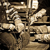 Close up of many hands tying a rubber pad to the rigging for one of the large steel trusses for The Palladium - Carmel, IN