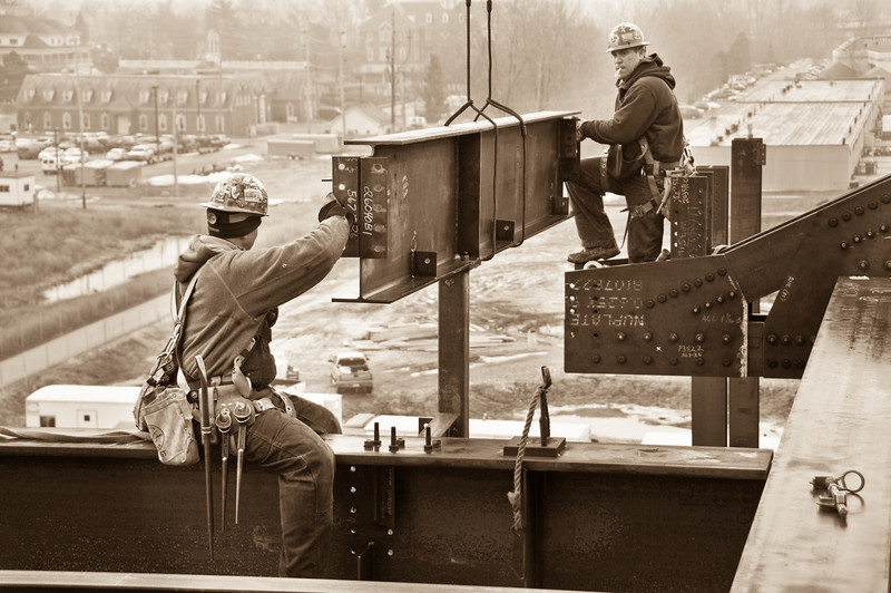 Two iron workers installing a steel beam on The Palladium - Carmel, IN