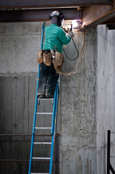 A lone working welding a beam to an embed plate in the concrete wall of The Palladium - Carmel, IN