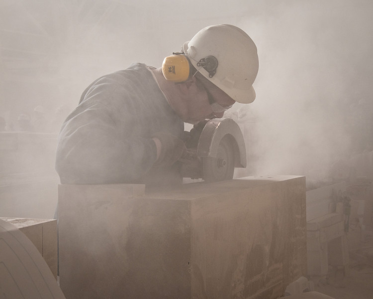 A limestone craftsman hand grinding details into one of the pieces of limestone for The Palladium - Carmel, IN