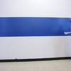 """John Ormonde of Lowell, a painter with UML's Operations & Services, touches up newly painted """"UMass Lowell Blue"""" stripes at Costello Gym where one coat was not enough. Sprucing up the lobby is in connection with the move to Division 1. (SUN/Julia Malakie)"""