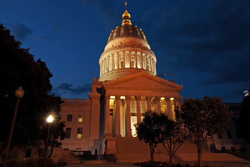 The gold domed State Capitol building in Charleston, WV, at night.