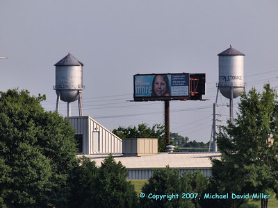 Water towers from a cotton storage facility, downtown Alexandria, Louisiana. Shot from the Pineville side of the Red River. Don't you love the billboard? I'll reshoot, I promise... Oly E330, ZD50-200 + EC14 Teleconverter