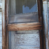 Old screen door and ratty curtains of an abandoned house in Kittitas County, in the state of Washington.
