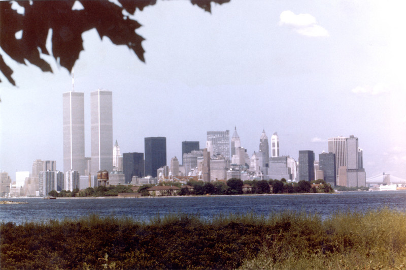 As shot from a print. From the 80s or 90s. Shot from the NJ side. Ellis Island is in front.