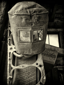 The mask of the welder hanging on the wall.