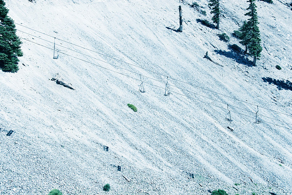 Diagonal debris lines of the steeply sloping embankment create a textured background for miniature carriages. Small patches of dark shadowed areas mimic the ski lift cables traversing up the mountain.