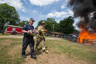 South Meriden fireman Hal Kevorkian left and Matt Montanye approach the fire to retire more American flags Sunday during the American Legion Post 45 Watch Fire ceremonies in Meriden Jun. 14, 2015 | Justin Weekes / For the Record-Journal