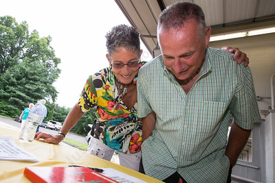 Oganizers Marcia Phelps and Chief Harold Clark look over an old photo from the Milldale School Saturday for the Milldale School Reunion at Engine Company 3 on Clark Street in Milldale Jul. 18, 2015   Justin Weekes / For the Record-Journal
