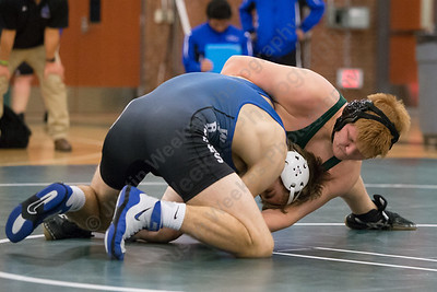 Maloney's Nikolas DeBaise tries to turn Hall's Justin Searls Wednesday during the season opener at Maloney High School in Meriden December 13, 2017 | Justin Weekes / For the Record-Journal