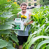 Brad Ray of Lynn, a member of the Food Projects' Community Supported Agriculture program which allows contributors to pick their own produce, walks through the community garden on Munroe Street with a freshly picked sunflower and other produce.