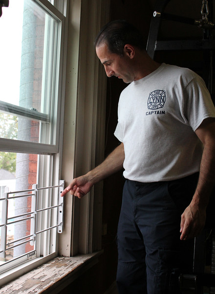 Lynn, Ma. 8-15-17. Lynn Fire Captain Tim Leighton demonstrates a child safety & window security guard that prevents window falls and keeps intruders out.