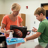 Lisa Pilat and her son Maddoc, 10, both of Dedham, pick out a binder and folders for back to school at LHAND on Tuesday.
