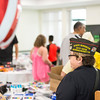 Christine Tron of the State Surgeon Department of Massachusetts looks on as kids and parents pick up back to school items during LHAND's Back to School Bash for veterans, military families, and Gold Star families on Tuesday.