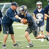 08/18/2017. Lynnfield football practice. Assistant coach John O'Brien hands the ball off to Cameron Lanza.