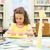 Marjorie Miceli, 3, of Lynnfield rolls a piece of construction paper into the shape of a giraffe's neck as she works to create a giraffe at the End of Summer Reading Party at Lynnfield Public Library.