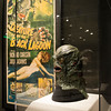"""A Gill-man prop head from Revenge of the Creature, 1955, with the poster for the film in the background on display in the """"It's Alive!"""" exhibit at the Peabody Essex Museum."""