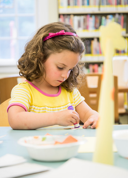 Marjorie Miceli, 3, of Lynnfield puts glue on a paper giraffe head as she creates a giraffe during the End of Summer Reading Party at Lynnfield Public Library.