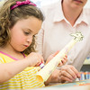 Marjorie Miceli, 3, of Lynnfield puts glue on the neck of her giraffe so she can add spots during the End of Summer Reading Party at Lynnfield Public Library.