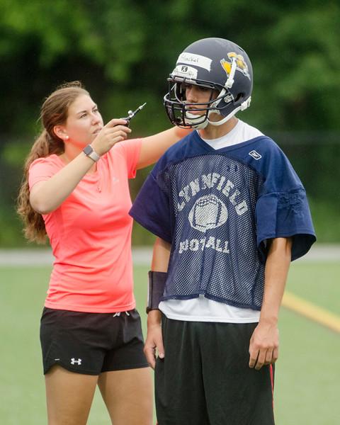 08/18/2017. Lynnfield football practice. Athletic trainer Courtney Blake adjusts the helmet of Owen Blacker.