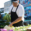Juan Tejera of Riverdale Farm in Groton, Mass., cleans up cauliflower as he helps set up for the farmer's market.