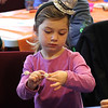 Amalia Ayube makes a food stick at the noon years evve celebration at the Saugus Library today. Photo by Owen O'Rourke