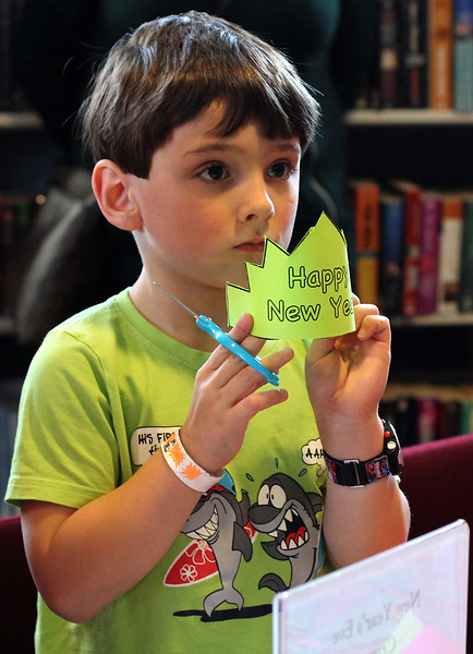 All of the kids attending the noon years eve celebration at the Saugus Library, like Finnegan Ayube, got the opportunity to make a paper crown. Photo by Owen O'Rourke