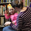 Kyla Ware shows her new crown to Tracey Owram during the noon years eve celebration held at the Saugus Library. Photo by Owen O'Rourke
