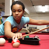 Destiny Rodriguez takes a shot using the aid of a pool rack in the teen room at the Boy's and Girl's Club on Lynn on Wednesday. The folks from RAW Arts are designing and paintng the walls in this room.Photo by Owen O'Rourke
