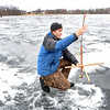 Peabody, Brown's Pond. Ice Fishing.<br /> Ryan Dempsey, who grew up in Peabody and now lives in Reading, returns to fish on Brown's Pond with his brother and a high school friend.  He is setting a trap for pickerel.