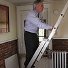 Ed Hayden climbs the ladder leading to attic in his office at 7 Franklin Street. Photo by Owqen O'Rourke