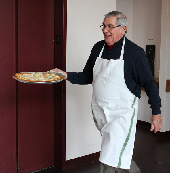 John Pace brings one of a pizza pie to the 3rd annual pie sale held by the Lynn Housing Authority & Neighborhood Development at Caggiano Plaza in Lynn to celebrate National Pie Day and to raise money for the outreach fund.  Photo by Owen O'Rourke