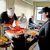 Buffet table. Lisa Archung, Peabody, waits as Julio Tavarez, Salem, carves a slice of meat.